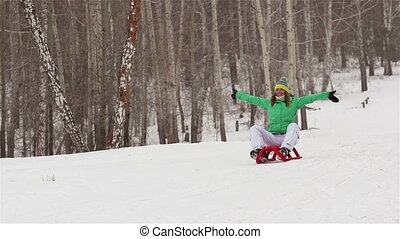 Joyful Ride - Joyful girl sledding down the hill slope