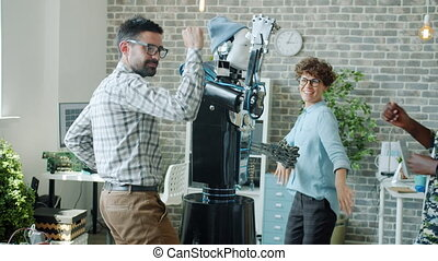 Joyful robotic engineers dancing with intelligent human-like robot in office