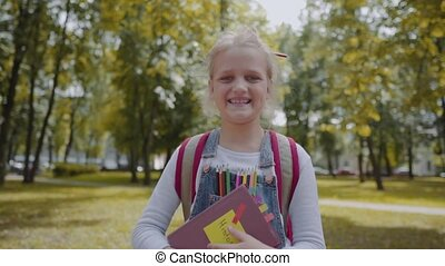Joyful schoolgirl with backpack holding a book staying in ...