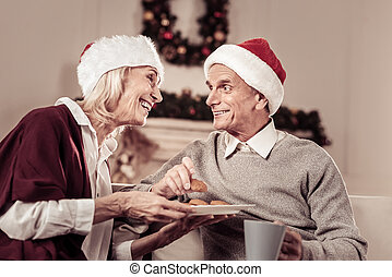 Joyful senior couple smiling and eating cakes.