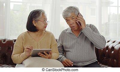 Joyful Senior couple using technology device at home