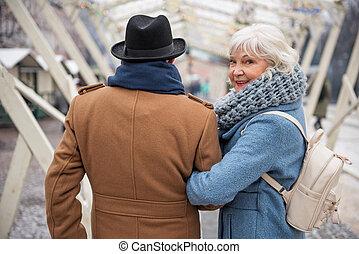 Joyful senior lady enjoying walk with her husband