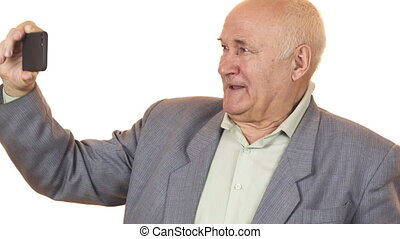 Joyful senior man smiling taking selfies with a smar phone