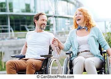 Joyful senior wheelchaired couple enjoying walk in the park