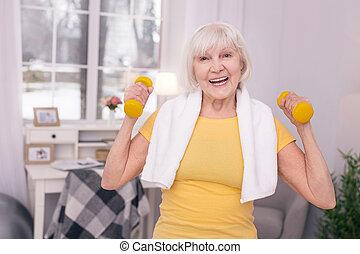 Joyful senior woman lifting up dumbbells and smiling