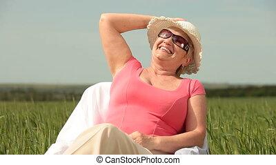 Joyful senior woman on green meadow