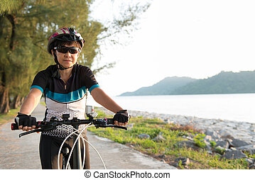 Joyful senior woman riding a bicycle