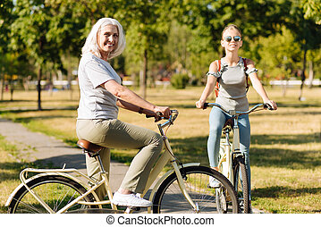 Joyful senior woman riding a bicycle with her granddaughter