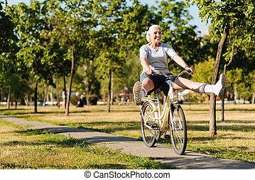 Joyful senior woman riding a bicycle