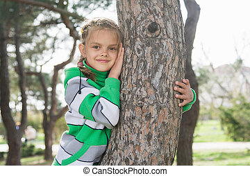 Joyful seven-year old girl sitting on a tree trunk in the early spring