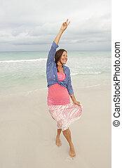 Joyful sexy mature woman beach holiday