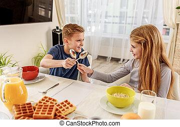 Joyful siblings having fun before breakfast
