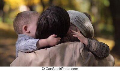 Joyful siblings hugging and kissing mom in park
