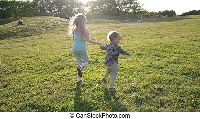 Joyful siblings running through green grassy field