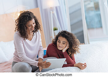 Joyful sisters watching film on touchpad together - Family...