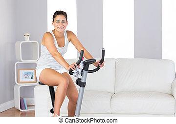 Joyful slim woman smiling at camera while training on an exercises
