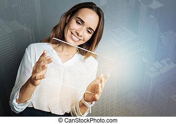 Joyful smart woman looking at the tablet screen