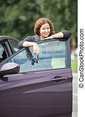 Joyful smiling Caucasian woman standing behind car door with key