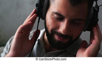 Joyful smiling man listening to music in his headphones