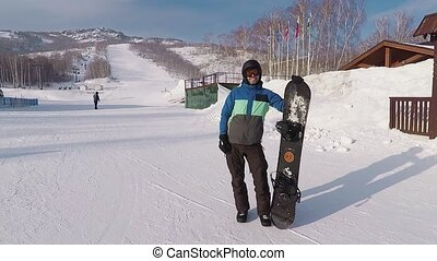 Joyful snowboarder stands and holds his snowboard on a background of hills from which he had just descended. Young man dressed in warm winter clothes shows gesture thumb up.