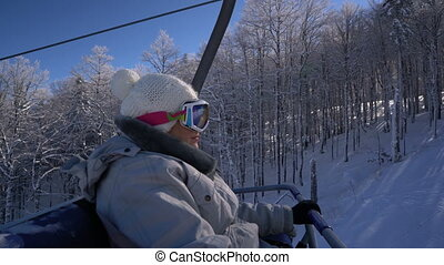 joyful snowboarder woman rises on the lift to the top of the...