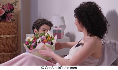 Joyful son giving bouquet of tulips to dear mother -...