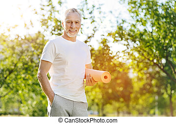 Joyful sporty aged man standing in the park