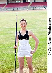 joyful sporty woman holding a javelin standing in a stadium