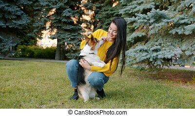 Joyful student caressing welsh corgi doggy in park on lawn ...