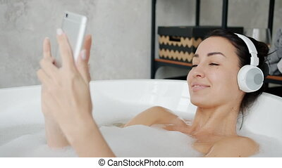 Joyful student wearing headphones is listening to music and touching smartphone screen in bathtub. Modern devices and youth culture concept.