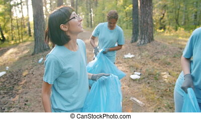 Joyful students multi-ethnic group picking litter in forest ...