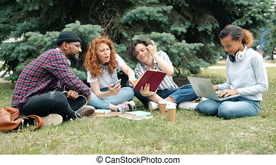 Joyful students studying outdoors with books and laptop chatting on grass