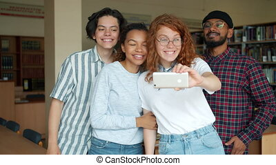 Joyful students taking selfie in library with smartphone having fun together