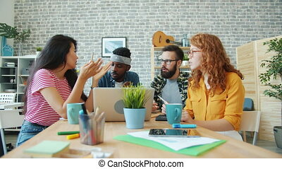 Joyful team of office workers talking looking at laptop screen working together