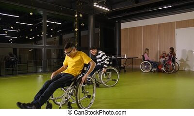 Two excited teenage boys with cerebral palsy competing with each other in wheelchairs. Cheerful teenagers making a race while other disabled people communicating on background