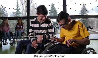Joyful teen boys with cerebral palsy using tablet