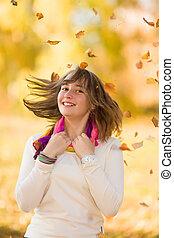Joyful teen girl having fun in falling leaves