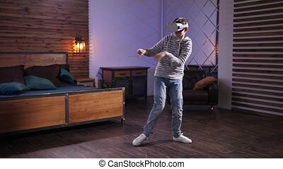 Joyful teen in VR goggles performing funny dance