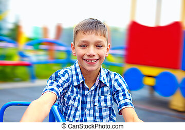 joyful teenage boy having fun on roundabout, playground