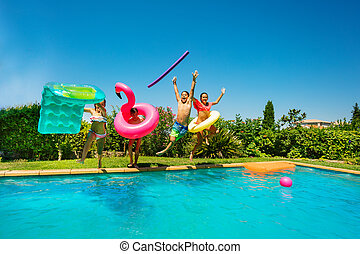 Joyful teens with swim tools jumping into the pool