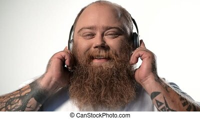 Joyful thick guy listening to favorite song