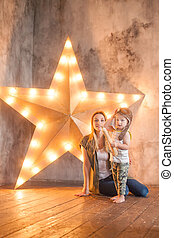 Joyful toddler kid with his mother on star studio background