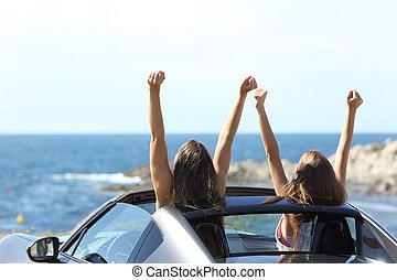 Joyful tourists watching the sea in a convertible car
