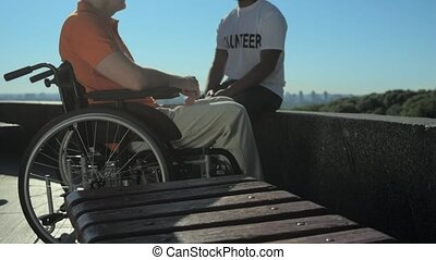 Joyful volunteer talking with a wheelchaired man