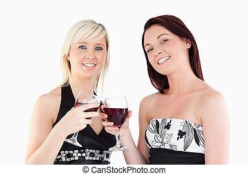 Joyful well-dressed women toasting with red wine