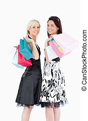 Joyful well-dressed women with shopping bags