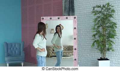 Joyful woman checking her body shape in mirror