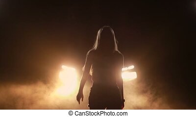 Joyful woman dancing in car headlights at night - Silhouette...