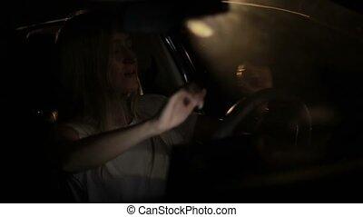 Joyful woman enjoying music in car at night - Sensual woman...
