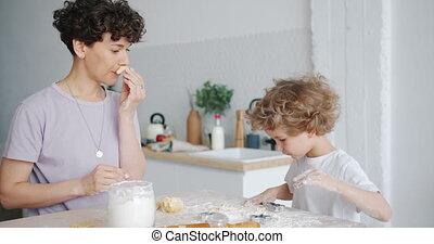 Joyful woman having fun with dough making moustache showing tongue to kid
